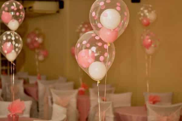 Centro de mesa feito com balões de gás hélio um dentro do outro para decoração chá de bebê