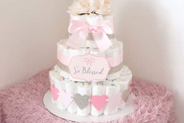Bolo de fraldas rosa com fitas de cetim para decoração chá de bebe faça você mesmo