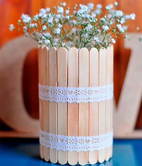 Centro de mesa com flores feito com palito de picolé preso por uma fita de renda
