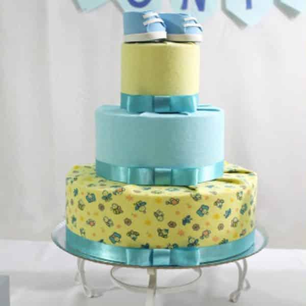 Bolo de chá de bebê amarelo e azul com sapatinho feito de EVA no topo