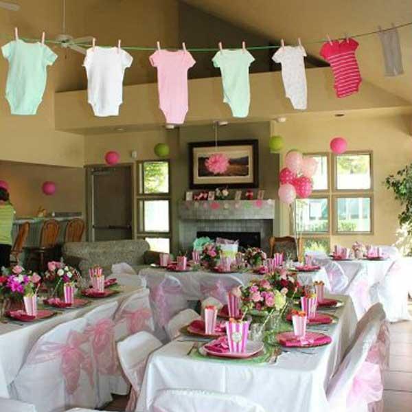 Varal de roupinhas de bebê sobre a mesa dos convidados no chá de bebe